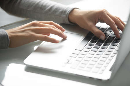 Workday in office. Close up of hands of millennial businesswoman worker employee client customer using laptop typing on portable computer keyboard searching information in internet working online