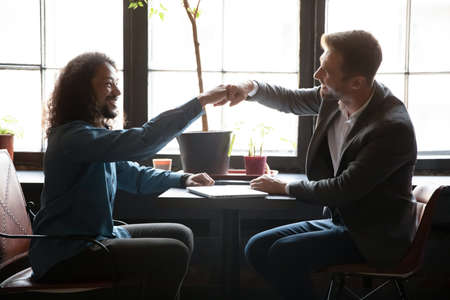 We have got it. Two happy excited young diverse men caucasian and biracial friends mates colleagues bumping fists above table at coffeehouse celebrating successful cooperation, achieving common goal 版權商用圖片
