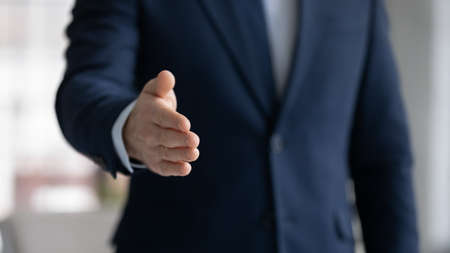 Close up crop image young businessman reaching out hand for shaking, proposing good deal to partner, making greeting gesture to client, welcoming new employee at work, congratulating with achievement.