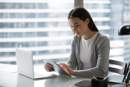 Modern office worker. Concentrated focused young businesswoman employee manager doing electronic paperwork at workplace using devices comparing checking synchronizing data at pad and laptop memory