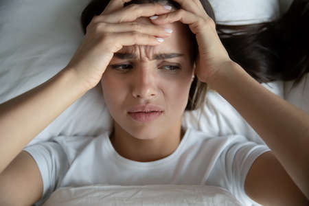 I did not get any sleep. Top view of exhausted unhappy millennial woman hugging head with bitter look lying in bed after sleepless night suffering of sudden migraine headache attack catching cold flu Stock Photo