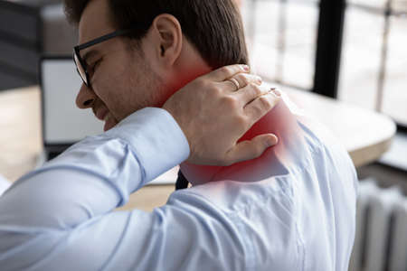 Rear view unhealthy millennial male manager worker touching inflamed place, suffering from strong neck pain, chronic ache muscular tension or nerve entrapment, sedentary office lifestyle concept.