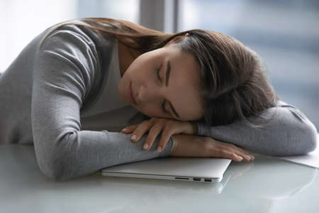 Sleepyhead. Tired millennial woman student employee manager sleeping napping on work desk putting head on hands feeling exhausted after hard study long workday sleepless night, overworked with gadget