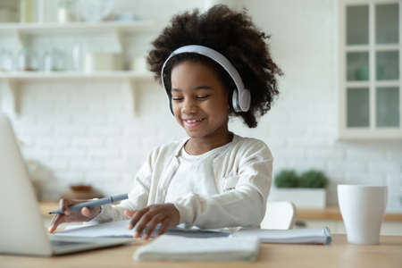 Smiling African American little girl wearing headphones studying at home, sitting at table with laptop and notebooks, writing notes, watching webinar, listening to lecture, homeschooling concept