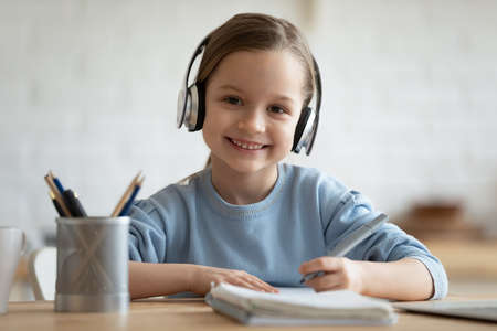 Head shot portrait smiling little girl wearing headphones looking at camera, sitting at table, studying at home, happy pretty child doing homework, holding pen, writing notes, watching webinar Foto de archivo