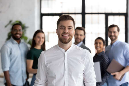 Smiling millennial student looking at camera posing for portrait in front of diverse young people group getting education at international university, happy ambitious intern receiving job at company Banco de Imagens