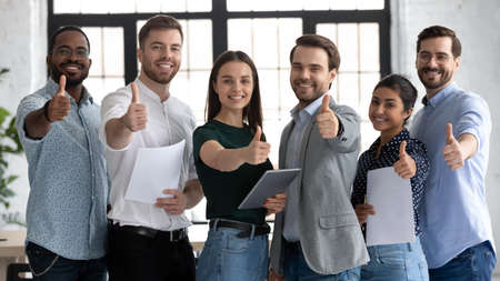 We are glad to recommend. Young modern team of diverse qualified specialists posing for portrait in corporate office looking at camera showing thumb up gesture approving product service able to help