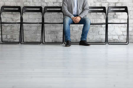 I might be next. Cropped shot of young male patient expecting for doctor appointment, confident unemployed specialist sitting on chair in empty row in calm pose waiting for meeting with hr, copyspace