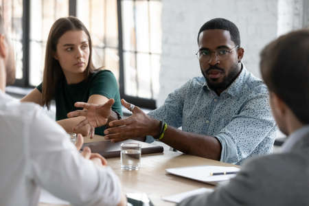 Capable black millennial male consultant advisor persuading group of clients in service or financial deal profit, young african businessman trying to get financial support for startup from investors