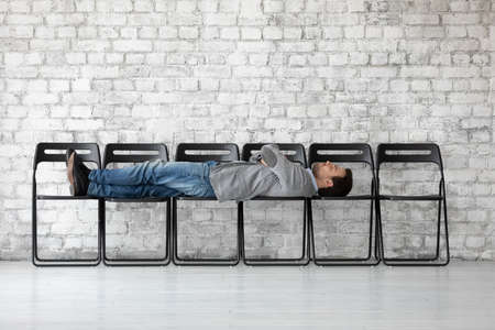 Bad time management. Bored young man applicant single candidate on vacant place lying on empty row of chairs before hr office sleeping dreaming relaxing while waiting for invitation on job interview 免版税图像