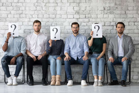 White male candidates are preferred. Group of multiethnic applicants sitting in row on job competition, three serious caucasian men looking at camera while other seekers hide faces under question mark Stok Fotoğraf