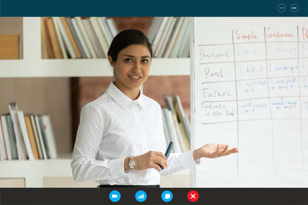 Smiling professional foreign language indian ethnicity female teacher standing near whiteboard, explaining grammar, giving educational lecture online to students, using video call meeting application. 免版税图像