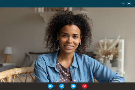 Head shot relaxed young african american attractive happy woman looking at web camera, enjoying nice pleasant weekend leisure remote talk with friends, using video call computer application at home.