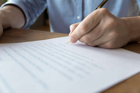 Man hand signing contract job agreement, close up view. Male client putting signature on legal document, take loan or mortgage in bank, real estate purchase, insurance or investment, make deal concept
