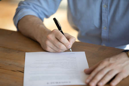 Man sit at table hold pen put signature on lawful agreement paper, subscribing name surname in statement with legal value. Hired employee signing contract agree terms and conditions, good deal concept Standard-Bild