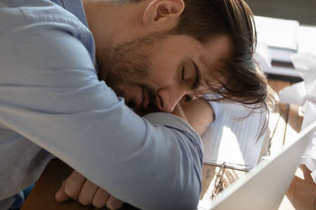 Close up business man put head on folded hands sleeping at workplace. Overloaded office employee tired of routine monotony paperwork. Unmotivated worker, insomnia and chronic fatigue syndrome concept Imagens