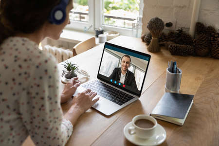 Rear view of female employee in earphones talk on video call on laptop with male client or colleague from home office. Woman have webcam online virtual meeting conference with coworker on computer.
