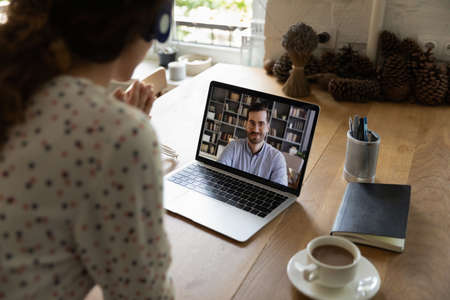 Rear view of woman worker look at laptop screen talk on video call with client or colleague at home office. Female employee have webcam digital virtual conference or online meeting with coworker. Stockfoto
