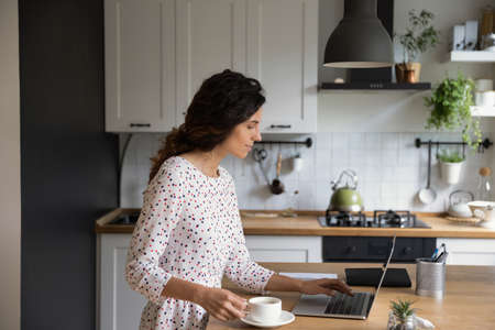 Young Caucasian woman stand in cozy modern renovated kitchen work on laptop drinking hot black coffee in the morning. Female employee look at computer screen busy browsing internet at home office.