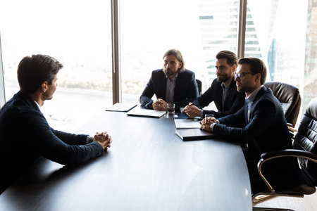 Businessmen sit at desk in boardroom talk discuss cooperation with client. Serious male recruiters employers have job interview with intern or work candidate at office meeting. Recruitment concept.