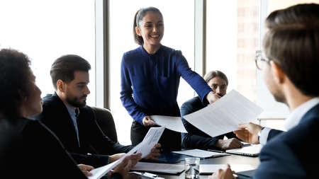 Wide panoramic view of smiling young businesswoman share handout material to colleagues at office meeting. Happy female leader spread give paperwork documents to businesspeople at briefing.