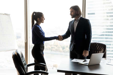 Young Caucasian businessman shake hand of happy female client or colleague close deal at office meeting. Happy business partners handshake get acquainted greeting at briefing. Cooperation concept. Stockfoto