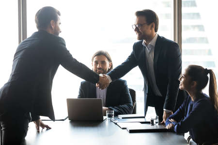 Smiling businessmen shake hands get acquainted greeting at meeting in office boardroom. Happy male business partners or clients handshake close deal or make agreement. Employment concept. Stockfoto