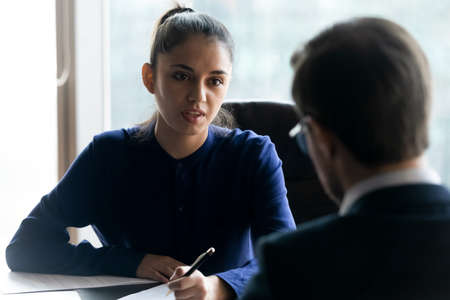 Serious young businesswoman talk with male colleague brainstorm cooperate at office briefing. Concentrated diverse business partners discuss company financial paperwork at meeting. Teamwork concept.