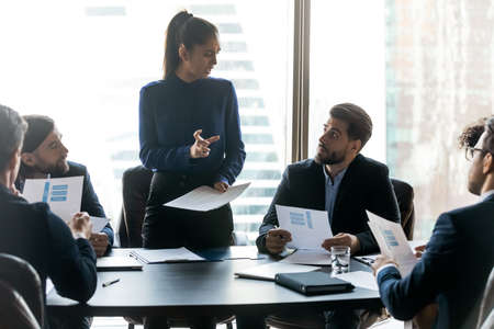 Confident young businesswoman stand lead head meeting with multiracial colleagues at office briefing. Successful female leader or boss talk brainstorm with diverse businesspeople at team meeting.