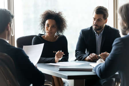 Focused multiracial businesspeople sit at desk at office meeting brainstorm consider paperwork together. Serious multiethnic diverse colleagues cooperate discuss financial project at team briefing.