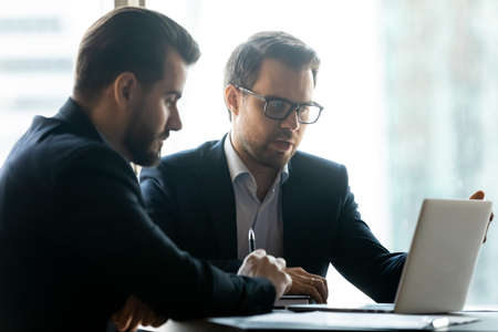 Focused Caucasian young male business partners or colleagues sit in office look at laptop screen brainstorm together. Serious businessmen work on computer talk discuss project. Cooperation concept. Stockfoto