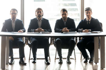 Portrait of serious businessmen sit at desk in office show confidence and leadership at workplace. Concentrated male employers executives ready for business interview. Employment, success concept.