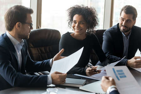 Smiling multiracial businesspeople sit at meeting talk discuss financial paperwork document together. Happy diverse multiethnic colleagues employees brainstorm discuss project. Teamwork concept. Stockfoto