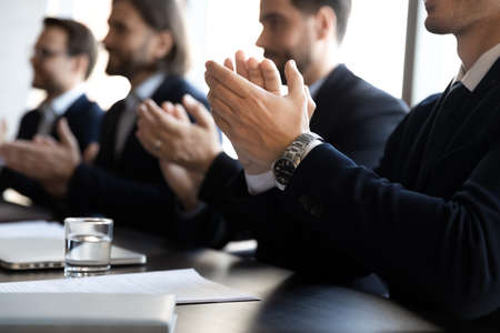 Crop close up of businessmen in formal suit sit ta desk in office applaud for presentation. Male employees businesspeople clap hands feel thankful for training. Appreciation, acknowledgment concept. Foto de archivo