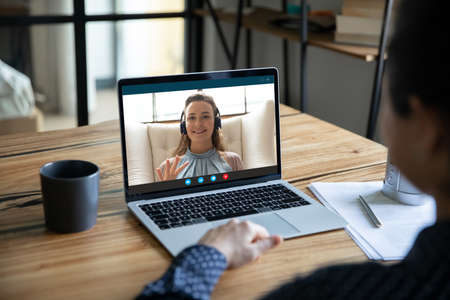 Shoulder back view young indian woman holding video call online meeting with smiling european female colleague in headphones, discussing working issues distantly, remote home office workday concept. Stockfoto