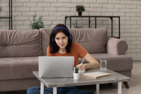 Happy interested young woman wearing headphones, involved in video call online educational lecture, watching presentation, studying on distant internet courses, self- education e-learning concept.