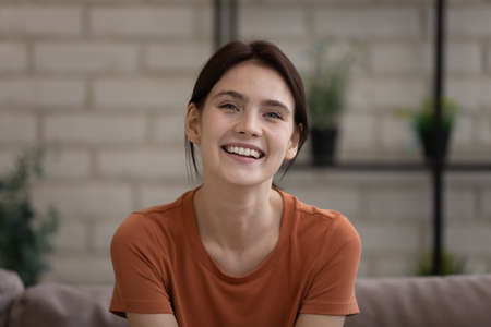 Head shot portrait of smiling millennial european woman resting on sofa at home, web camera view happy young lady enjoying online video call conversation with friends, entertaining alone indoors.