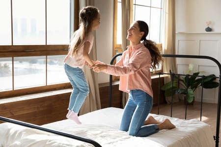 Cheerful sweet little girl hold loving caring mommy hands jumping on bed in light sunny cozy bedroom. Concept of happy motherhood and adopted child, active funny games with children at home concept