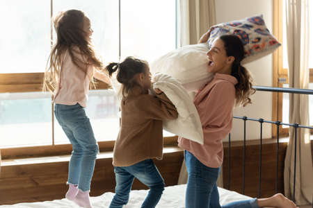 Crazy battle games with kids at home in morning. Young mom enjoy playtime with 2 preschool daughters fighting with pillows jumping on bed screaming feels excited, funny activity with children concept