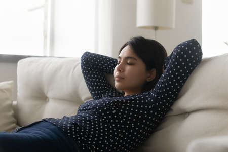 Close up peaceful Asian young woman sleeping on cozy couch at home, stretching, leaning back with hands behind head, tranquil attractive female with closed eyes resting on sofa, enjoying lazy weekend Banco de Imagens