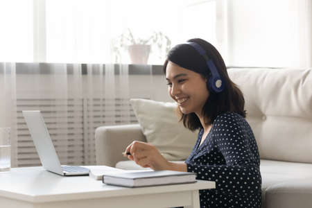 Smiling Asian young woman wearing headphones studying online at home, happy female student looking at laptop screen, watching webinar, listening to lecture, writing notes, e-learning concept