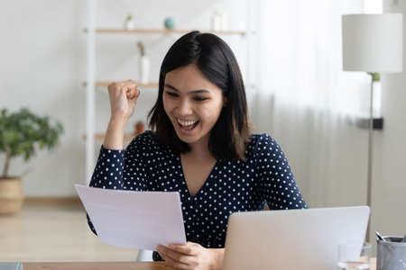 Close up overjoyed Asian woman reading good news in letter, holding paper sheet, celebrating success, job promotion, showing yes gesture, excited student received scholarship or great exam result