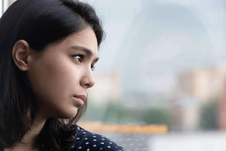 Close up frustrated thoughtful Asian woman looking out window, thinking about personal problems, upset unhappy female suffering from breakup or divorce, lost in thoughts, feeling lonely and depressed Banco de Imagens