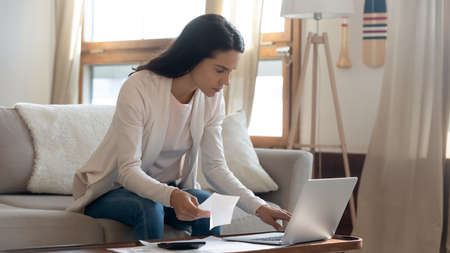 Easy to pay. Thoughtful young businesswoman sitting on couch by computer checking account online using e-banking app, focused millennial female paying monthly bills taxes from home office by internet