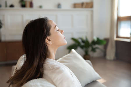 Minute for myself. Happy serene young lady taking pause in daily routine meditating on sofa with closed eyes breathing cool fresh air satisfied with conditioning humidifying system work, copy space Stockfoto