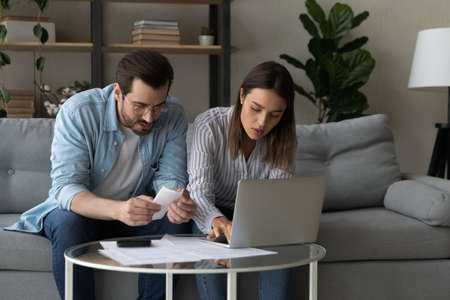 Focused young Caucasian couple busy calculating family budget paying bills taxes online on computer. Serious man and woman spouses manage household finances, consider expenses expenditures.