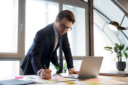 Confident busy young man in formal suit boss executive head of corporate branch checking controlling department work result studying statistic information from financial report and electronic database