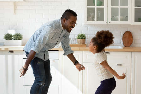 Funny cooking with dad. Happy laughing millennial black father dancing disco at modern designed kitchen with overjoyed little kid daughter jumping listening to music enjoying active leisure having fun