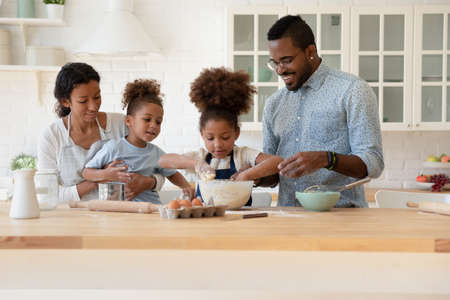 Family recipe. Happy african family mother, father and younger son watching with interest affection elder daughter kneading dough, black parents and small children baking holiday cake at home together 版權商用圖片