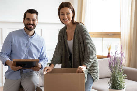 Portrait of smiling young Caucasian couple unpack personal belongings from cardboard box moving together. Happy man and woman renters unbox packages parcels with things relocate to own new home house.